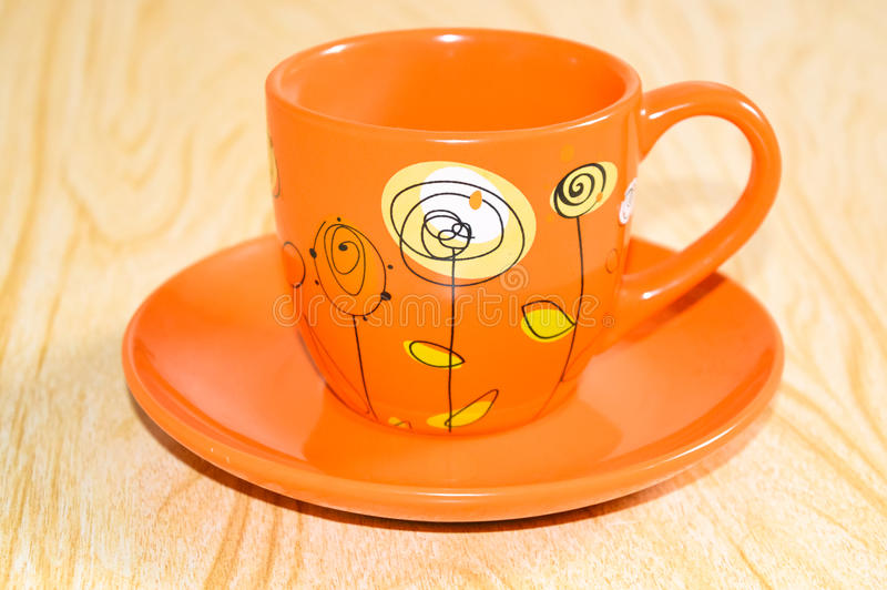 Orange Cup on a saucer. Beautiful, bright orange Cup with a pattern on a saucer from the tea couple royalty free stock photos