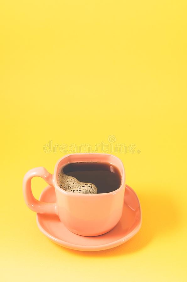 Orange cup with a saucer full of black coffee on a yellow background/orange cup of espresso with a skin on a yellow background. Orange cup with a saucer full of royalty free stock photography