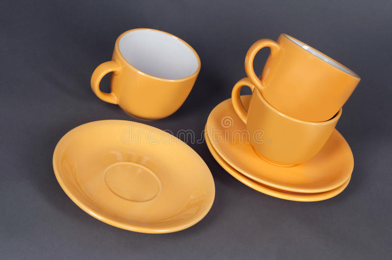 Orange cup and saucer. Isolated on a gray background stock photos