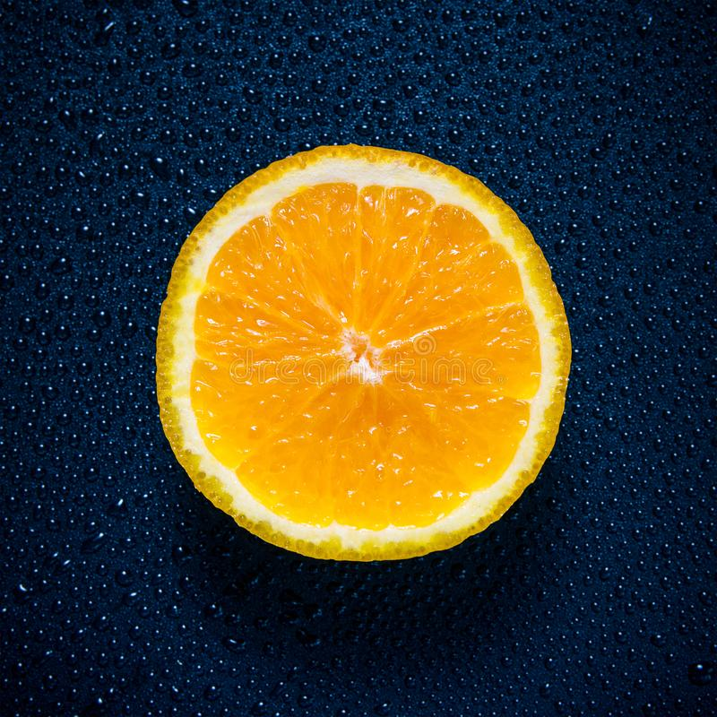 Orange cut in half close up shot with water droplets creating texture royalty free stock photos