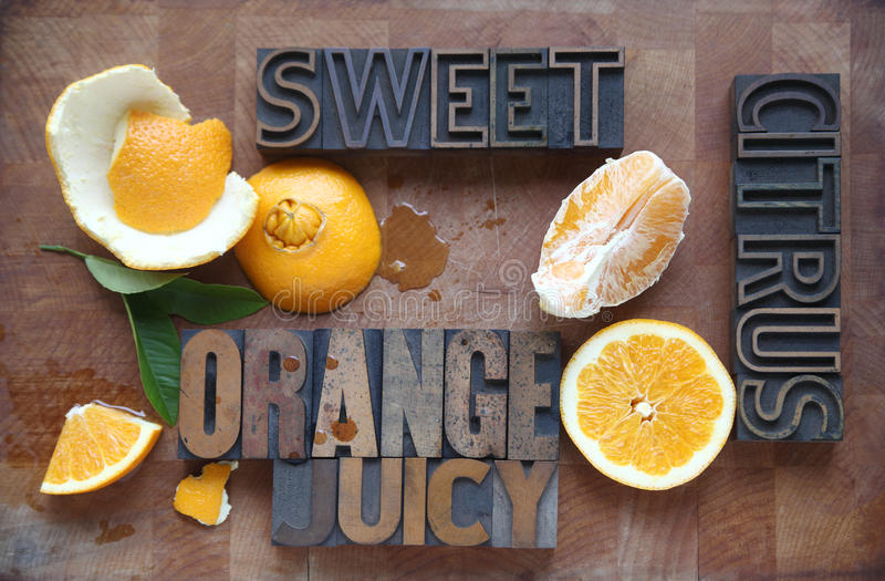 Orange cut and peeled with related words. A navel orange with peeled, halved, and cut sections and descriptive words with spilled juice on a cutting board royalty free stock images