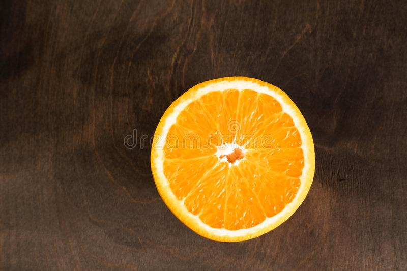 Orange cut rests on dark wooden table royalty free stock photos