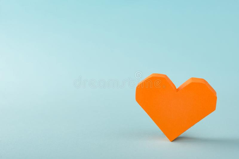 Orange 3D paper heart. On light blue background with copy space. Love, St. Valentine`s Day concept stock photos