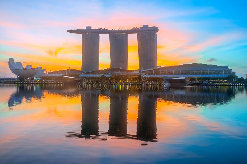 Orange Dawn at Marina Bay. Morning in Singapore. Three buildings of the hotel in the form of a ship are reflected in the calm water of Marina Bay. The rising sun stock photo