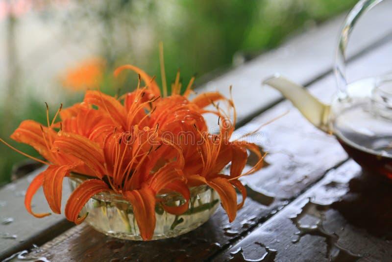 Orange Daylilyblommor och tekanna på en tabell arkivfoto