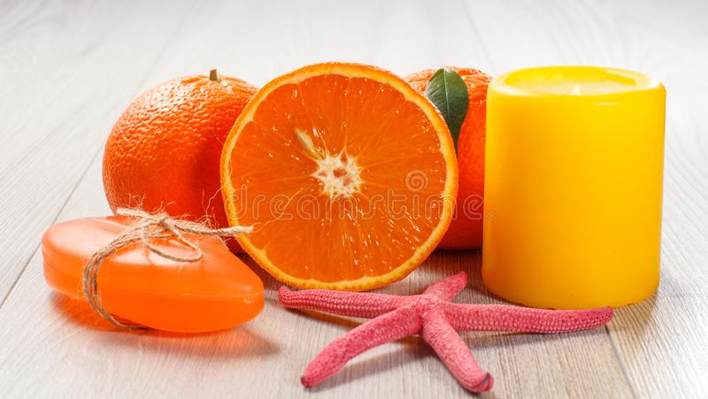 Orange de coupe avec deux oranges entières, savon, étoiles de mer et bougie brûlante photographie stock libre de droits