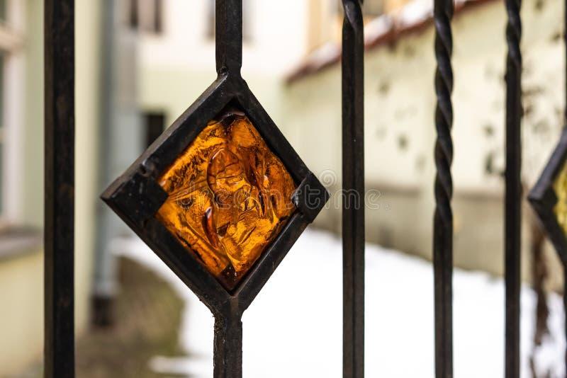 Orange dekoratives Buntglaselement im Metallzaun stockfotografie