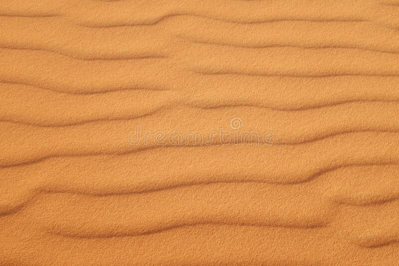 Orange desert sand patterns of the Arabian Desert for a warm summer background stock photo