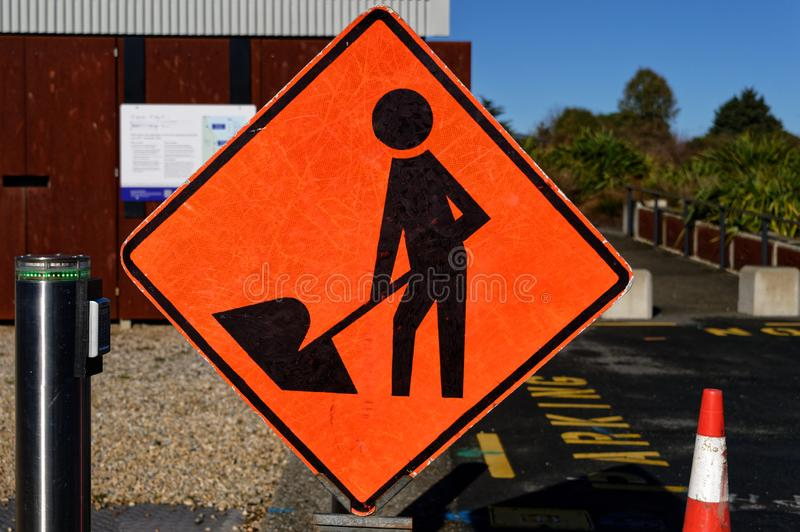 A man at work sign is positioned to warn people of possible danger. An orange diamond sign with a figure of a person at work warns of potential danger royalty free stock images
