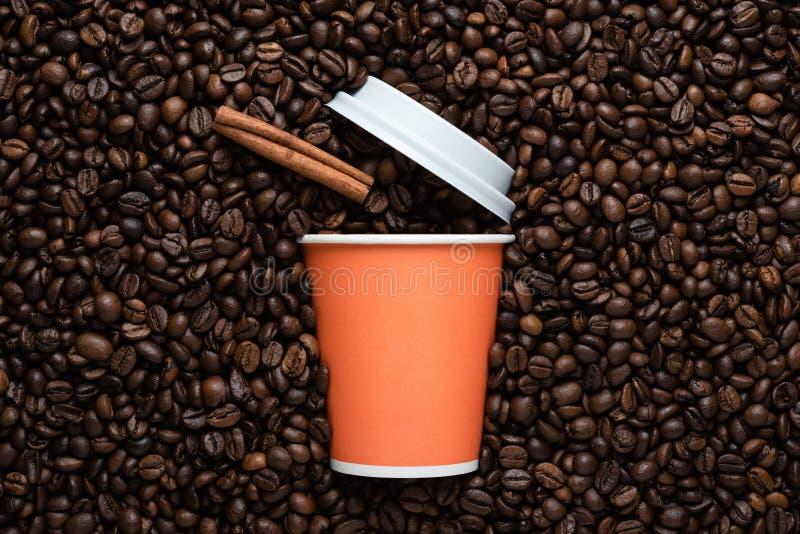 Orange disponibel kopp kaffe som går med en kanelbrun pinne på bakgrunden av grillade bönor arkivbild