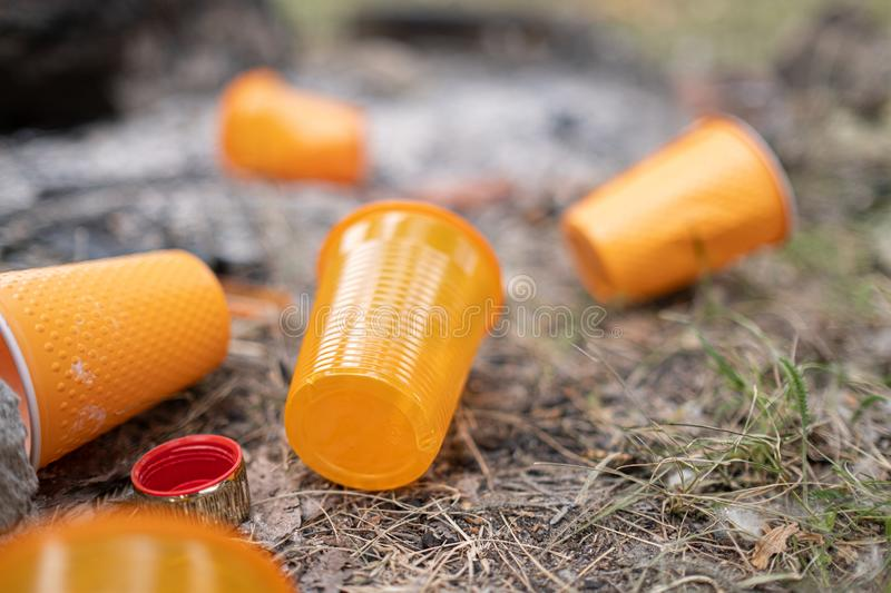 Orange disposable Plastic glass or cups used for drinking water in a bin - Environmental problem concept. Non-compostable waste stock photos