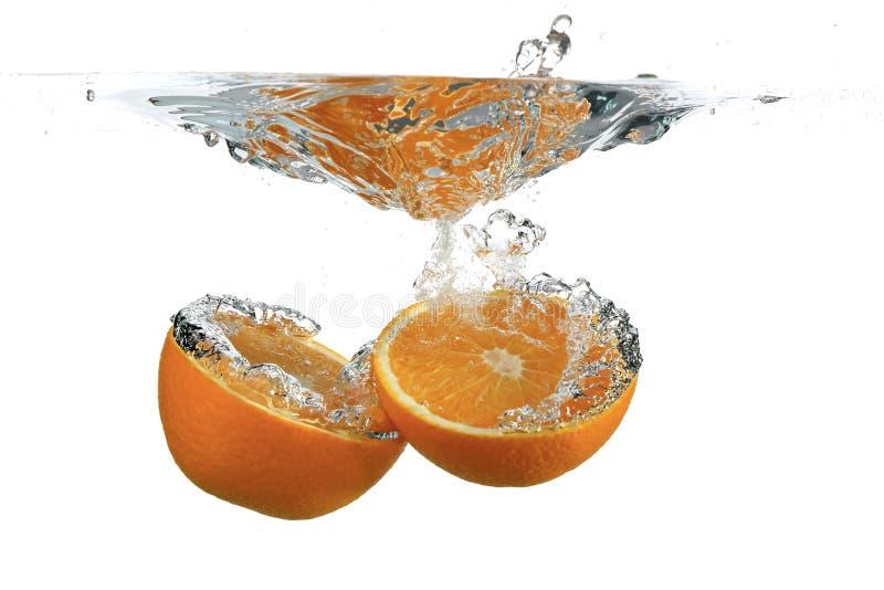 Orange divisée dans l'eau photos stock