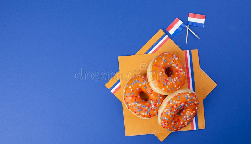 Orange donuts for the holiday King`s Day, Holland holidays. Baking on a blue background. Top view. Copy space. stock image