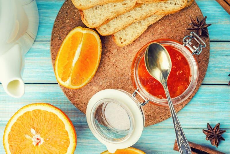 Orange driftstopp i den glass kruset, rostade bröd och stycken av apelsinen på blå träbakgrund arkivbild