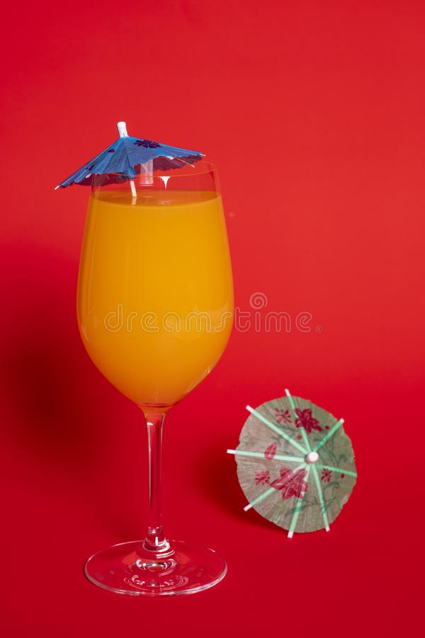 Orange Drink in Wine Glass Against Red II. Orange drink with a blue umbrella in a wine glass set against a solid red background. A green umbrella lies beside the stock image