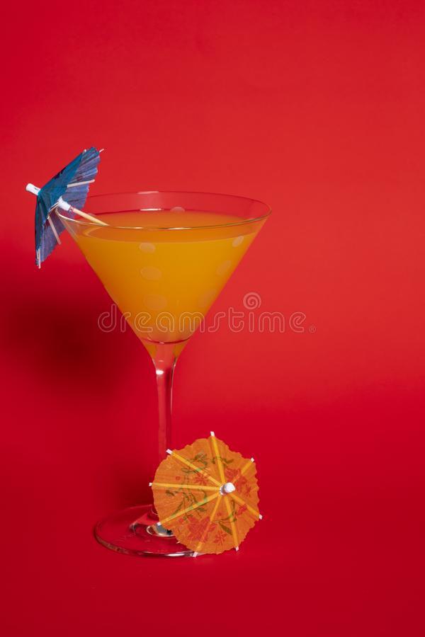 Orange Drink in Martini Glass Against Red. Orange drink with a blue umbrella in a martini glass set against a solid red background. An orange umbrella lies at stock photo