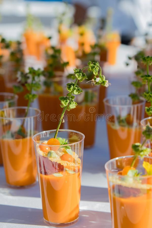 Orange drinks with Basil. Glasses with orange liquid and a stirrer of basil blossoms - Photographer: Steven Styles royalty free stock image