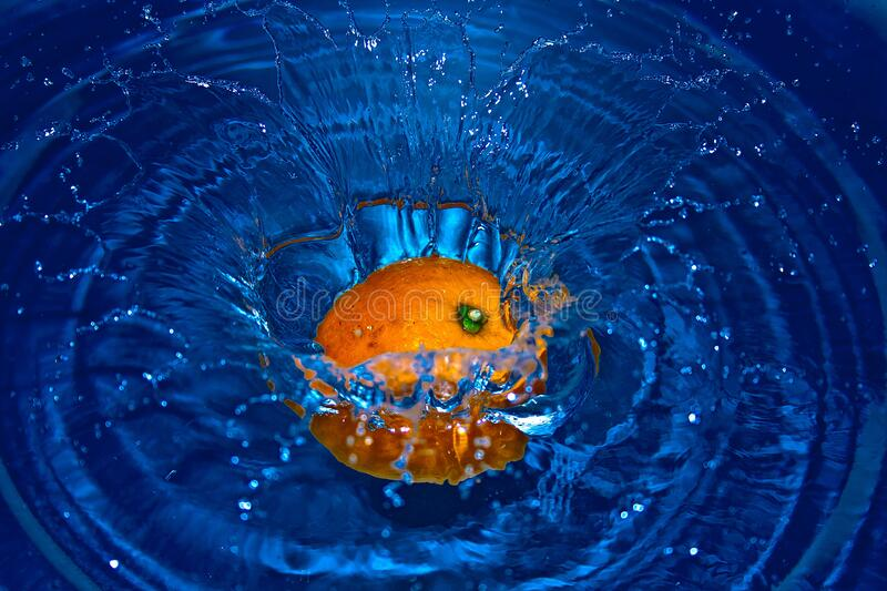 Orange Drop in Water in Time Laps Photography royalty free stock image