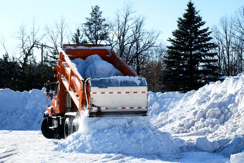 Orange dump truck empties a load of snow after several winter snow storms. In Minnesota royalty free stock images