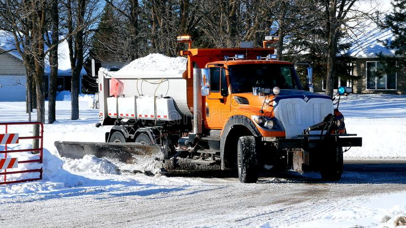 Orange dump truck with plow blade hauls a load of snow after several winter snow storms. Orange dump truck with plow blade turns corner as it hauls a load of stock photography