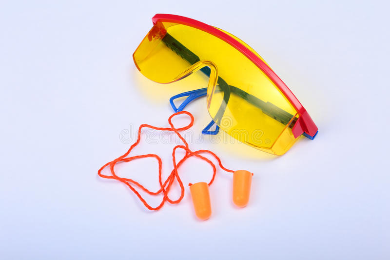 Orange earplug and safety glasses. Earplug to reduce noise on a white background . stock photos