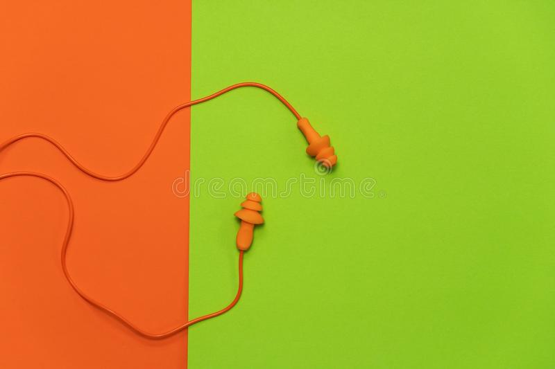 Orange earplugs for protect or reduce noise from loud environment pollution on colorful green background. Orange earplugs for protect or reduce noise from loud stock photo