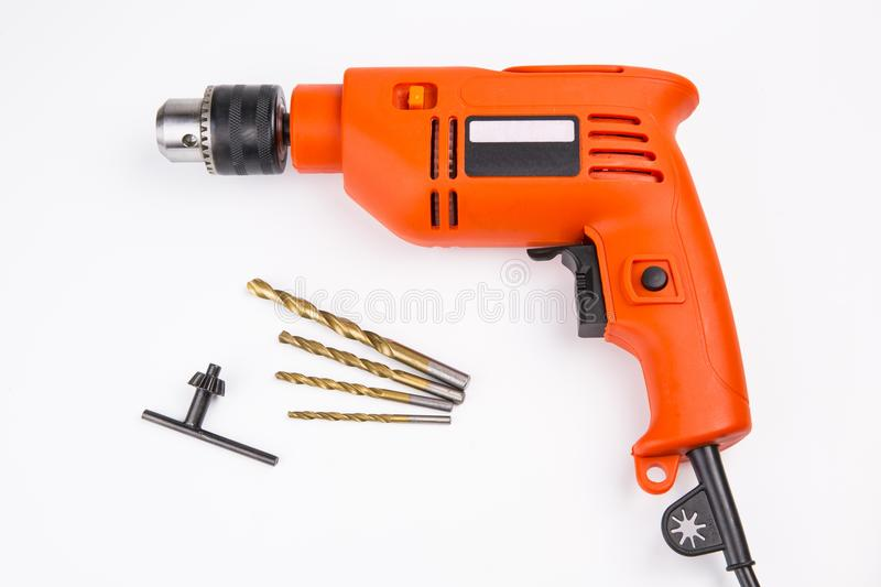 Electric drill. Orange electric drill with handle on white background royalty free stock image