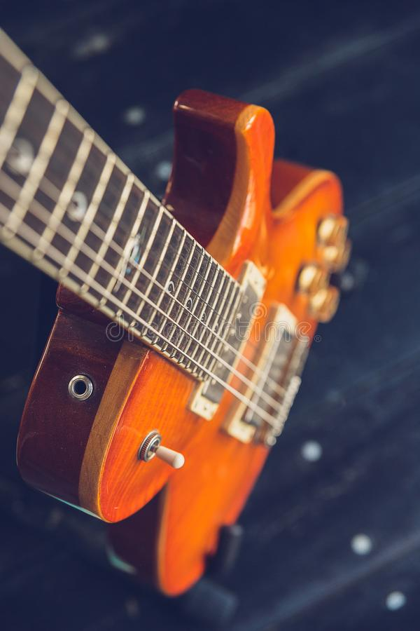 Orange electric guitar top view, an unusual angle of vertical. Focus on the part of the neck royalty free stock image