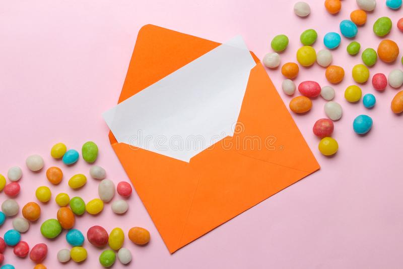 Orange envelope with a blank for text and colorful panting on a bright trendy pink background. top view stock photography