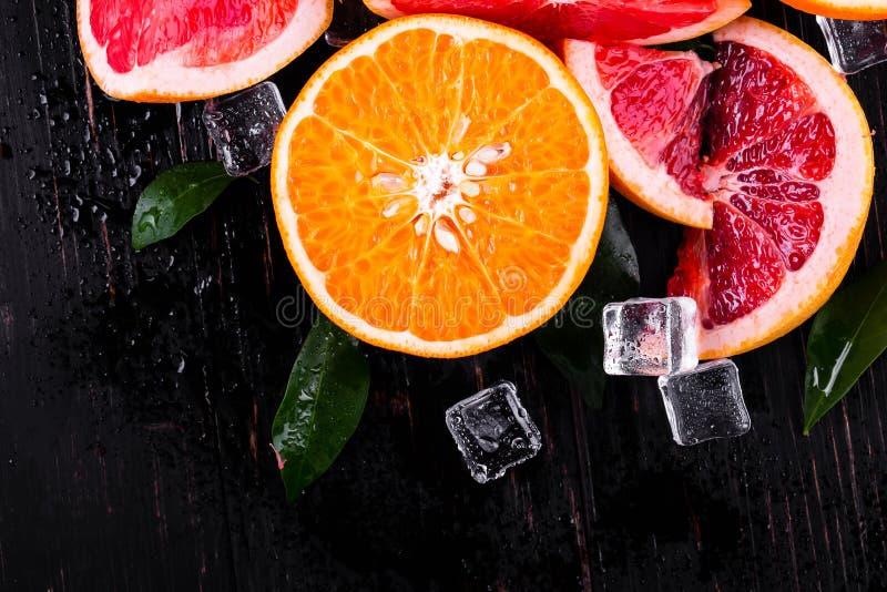 orange et jus de pamplemousse sur un fond noir en bois photos stock