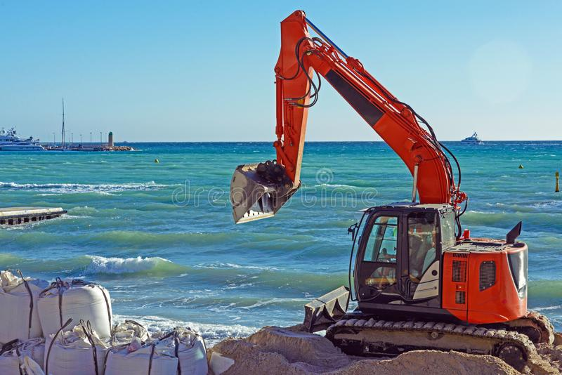 Orange excavator on the beach of the French city of Cannes against the background of the blue sea. Strengthening the coast. Protect famous Croisette from royalty free stock photos