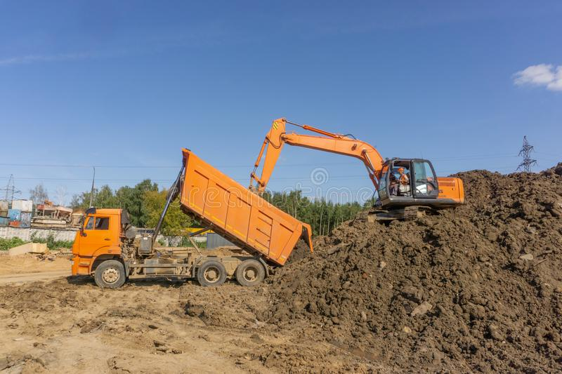 Orange excavator loads the land royalty free stock image