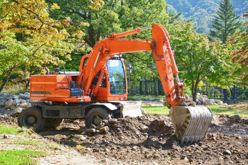 Orange excavator machine, backhoe digging soil. royalty free stock photography