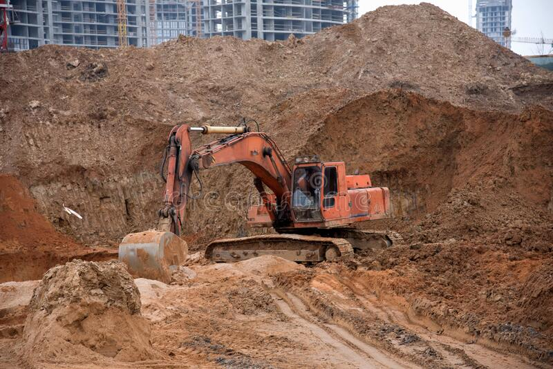 Orange excavator machine on earthworks in sandpit at construction site. Backhoe digs ground for construct foundantion. And laying storm pipes and water system royalty free stock photography
