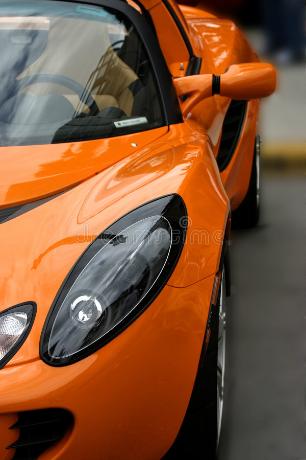 Orange exotic sports car. Side view of orange exotic sports car stock photo
