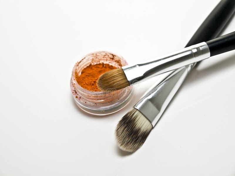 Orange eyeshadow. Orange eye shadow and cosmetic brushes stock photo