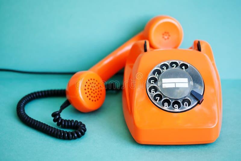Orange färg för upptagen retro telefon, handset mottagare på grön bakgrund Fältfotografi för grunt djup royaltyfri bild