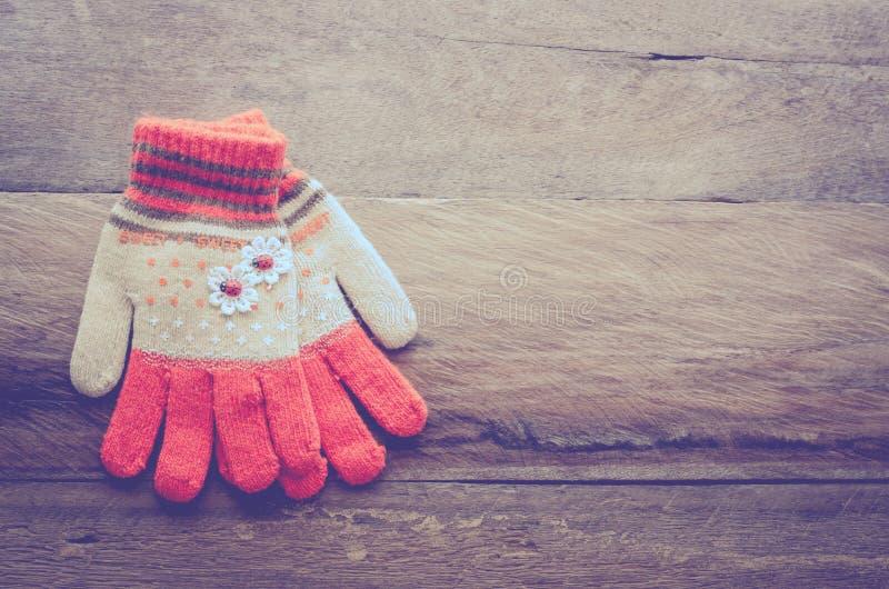Orange färg för vinterhandskar på träbakgrund - tona tappning arkivfoto