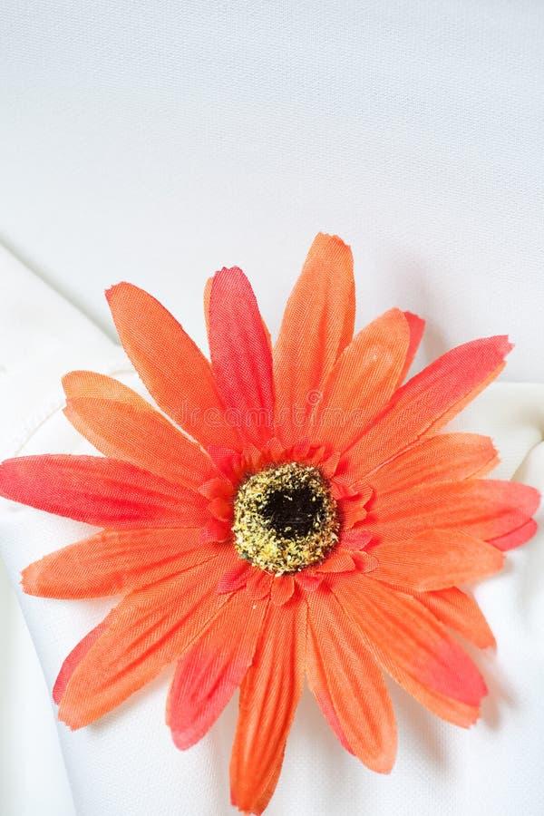 Orange fabric daisy on white linen