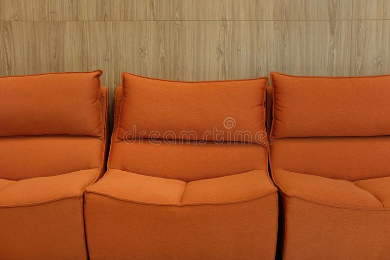 Orange fabric sofa couch furniture in living room. Near wood wall stock photography