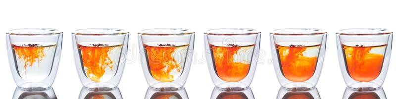 Orange Farbe verbreitet im Glas Wasser stockbild