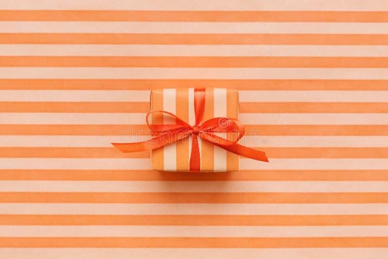 Orange Farbgeschenkbox mit Bogen auf gestreiftem Packpapier lizenzfreie stockbilder