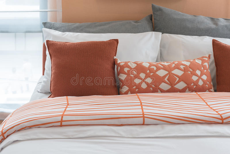 Orange Farbtonkissen stellten auf Bett im modernen Schlafzimmer ein lizenzfreies stockfoto