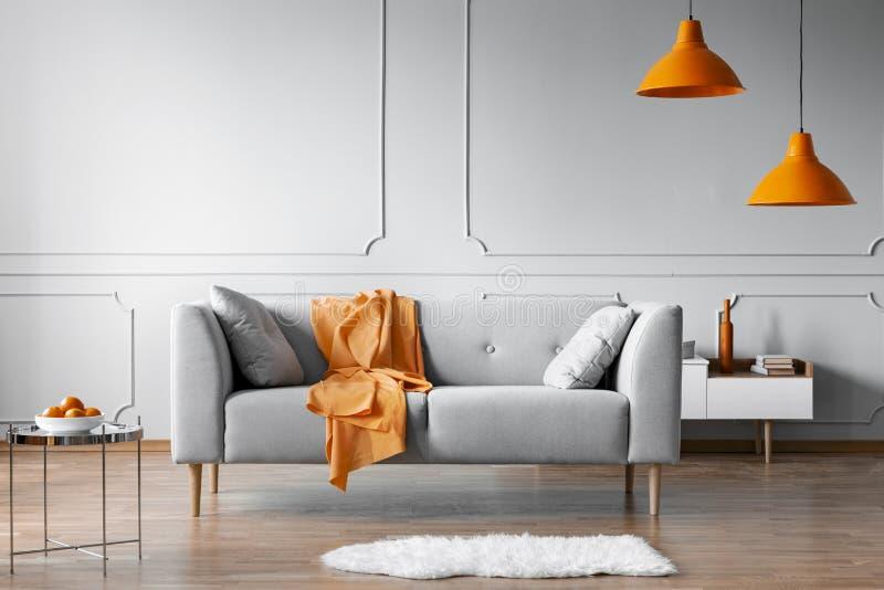 Orange filt på den gråa scandinavian soffan, kopieringsutrymme på den gråa vardagsrumväggen arkivfoton