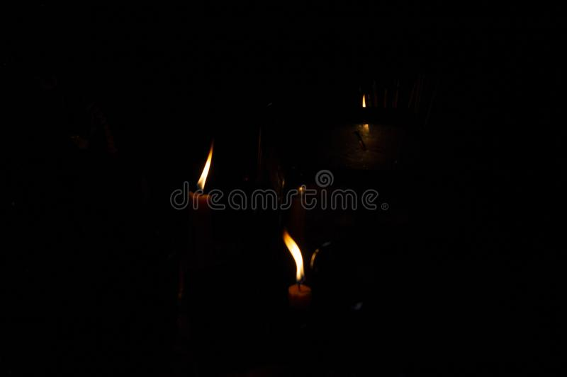 Orange fire of candles in darkness. Religious ritual of memory and pray. Human belief concept. In memoriam black banner template. Buddhist mantra reading stock photo