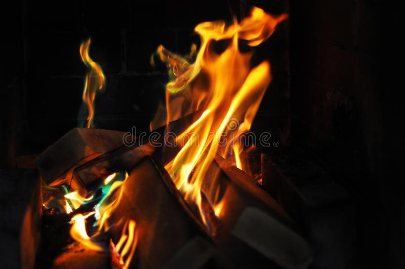 Orange fire flames in the dark fireplace. Cozy, warm home royalty free stock image