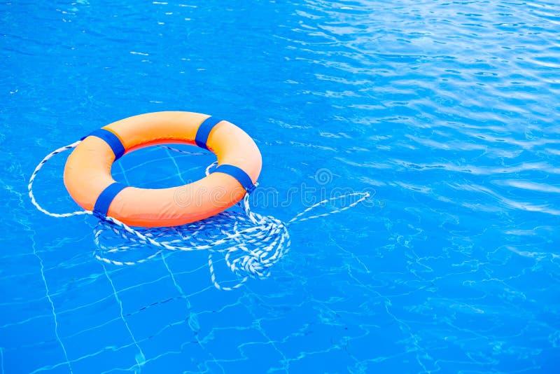 Orange flöte för livbojpölcirkel på blått vatten Livcirkel i simbassängen, livcirkel som överst svävar av soligt blått vatten arkivbilder