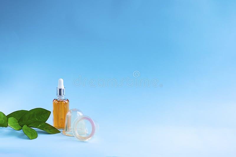 Orange Flasche des Modells mit Öl und zwei klaren Silikonschalen für Vakuummassage für Cellulite auf blauem Hintergrund Anticellu lizenzfreie stockbilder