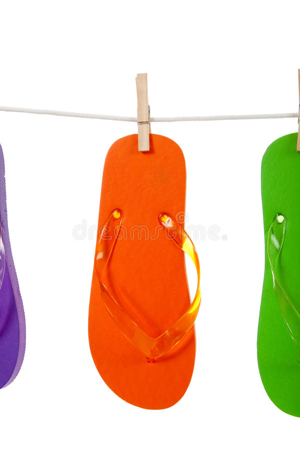 Orange flip - flop on clothesline. An orange colored flip-flop on a clothesline with a clothespin on a white background royalty free stock images