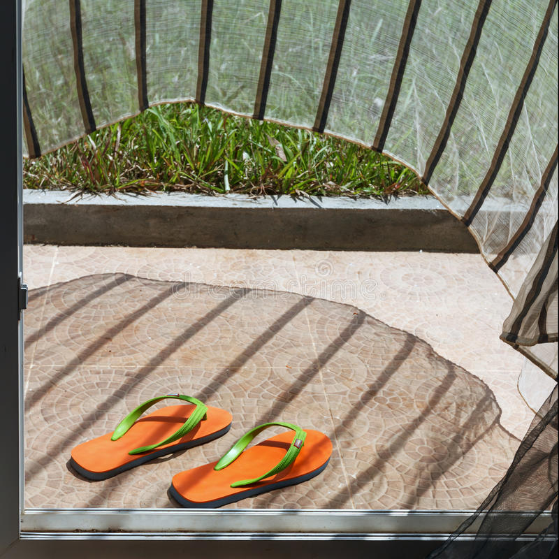 Orange flip-flops lying at a house entry. With waving curtain view 2 stock images